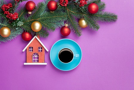 Hot coffee and pine branch with christmas toys on violet background. photo