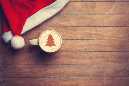 comida de navidad: Cappuccino con sombrero de navidad en la mesa de madera. Foto de archivo