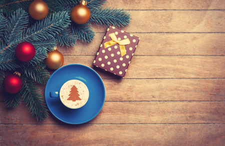 red cup: Cappuccino and gift with pine branch on wooden table.