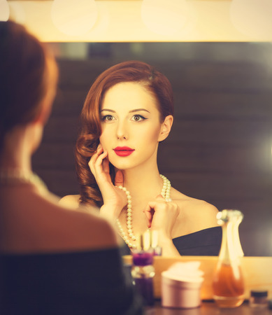 woman mirror: Portrait of a beautiful woman as applying makeup near a mirror. Photo in retro color style.