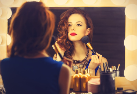 on mirrors: Portrait of a beautiful woman as applying makeup near a mirror. Photo in retro color style.