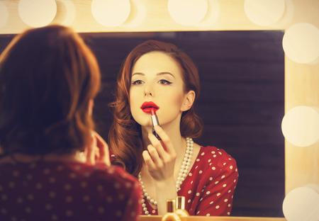 ミラーの近くの化粧を適用すると美しい女性の肖像画。レトロな色のスタイルの写真。