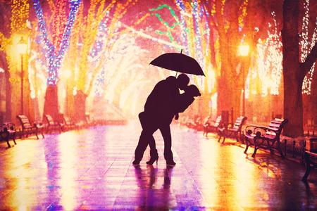 uomo sotto la pioggia: Coppia con ombrello baciare al vicolo di notte. Archivio Fotografico