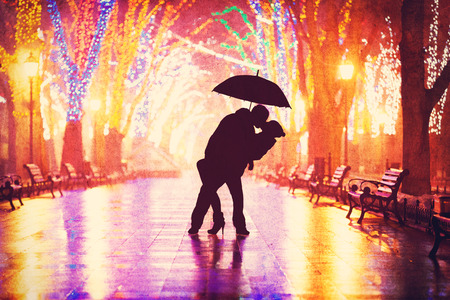 woman with umbrella: Couple with umbrella kissing at night alley.