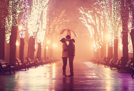 カップルは夜の路地で傘にキスします。