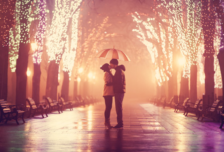 kissing: Couple with umbrella kissing at night alley.