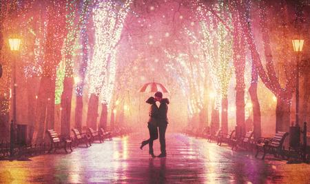 傘の夜の路地でキスをカップルします。