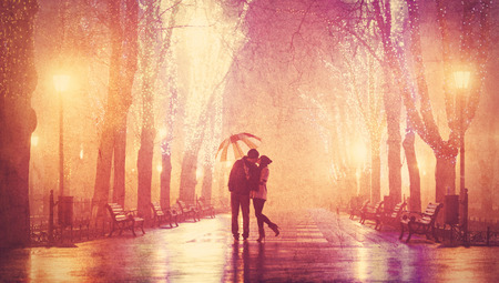 Couple with umbrella kissing at night alley. photo