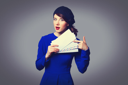 Portrait of beautiful women in blue dress with envelopes on grey background. photo
