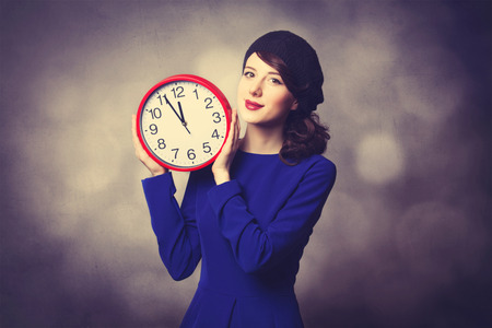 Portrait of beautiful women in blue dress with huge clock on grey background. photo