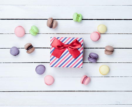 Sweet macaron and gift box on white wooden background photo