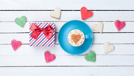 Cup of Cappuccino with heart shape symbol and cookies with gift box on white wooden background