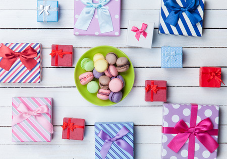 Gift boxes and french macaron on white wooden background photo