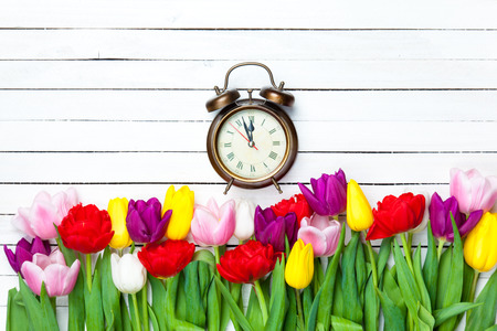 fresh flowers: Alarm clock and tulips on white background