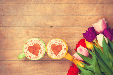 Two cups of Cappuccino with heart shape symbol and tulips on wooden background Imagens
