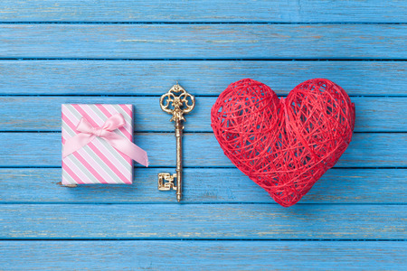 key box: Heart shape toy with key and gift box on blue wooden background. Stock Photo