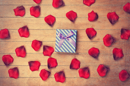 sexual pleasure: Gift box and petals on wooden table.