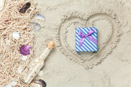 Net, shells with bottle and gift box on sand background. photo