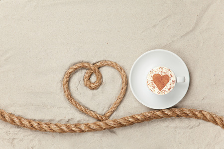 Cup of coffee near heart shape rope on sand background photo