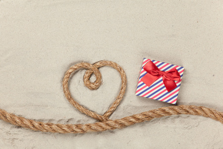 Gift box and rope in heart shape on sand background. photo