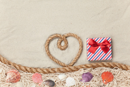 Gift box and rope in heart shape near net and shells on sand background. photo