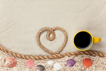 Heart shape rope and cup of coffee near net and shells on sand. photo