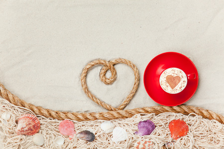 Cup of Cappuccino with heart shape symbol with net and shells on sand photo
