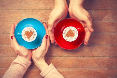 hombre tomando cafe: Mujer y hombre sosteniendo tazas de café con el símbolo de forma de corazón sobre un fondo de madera
