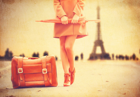 Gril in coat with umbrella and suitcase in Paris on Eiffel tower background