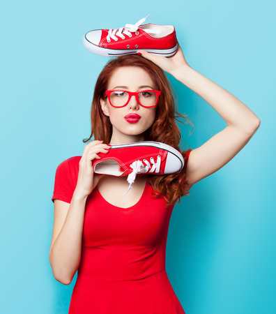 Surprised redhead girl in red dress with gumshoes on blue background.