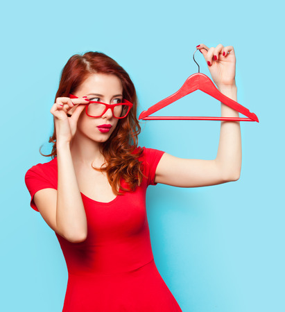 girl in red dress: Surprised redhead girl with hanger on blue background.
