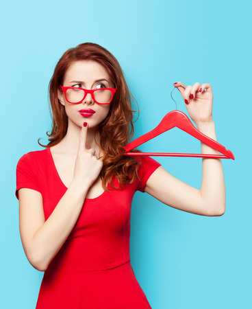 Surprised redhead girl with hanger on blue background.