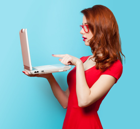 pelirrojas: Chica pelirroja sorprendida con el ordenador port�til sobre fondo azul Foto de archivo