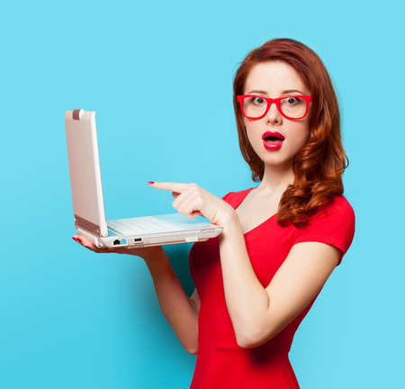 Surprised redhead girl with laptop on blue background Foto de archivo
