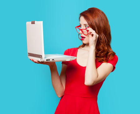 Surprised redhead girl with laptop on blue background Standard-Bild