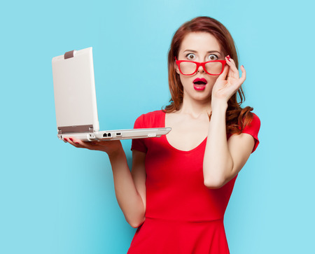 Surprised redhead girl with laptop on blue background Stockfoto