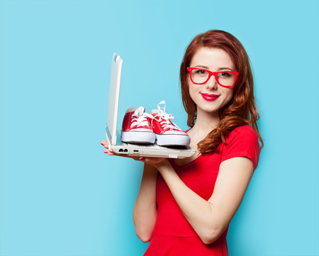 sale shop: Style redhead girl with gumshoes and laptop on blue background Stock Photo