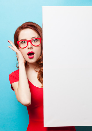 Surprsied student girl in red dress and glasses with white board on blue background