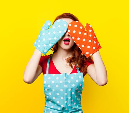 Chica pelirroja con guantes de cocina y delantal en fondo amarillo