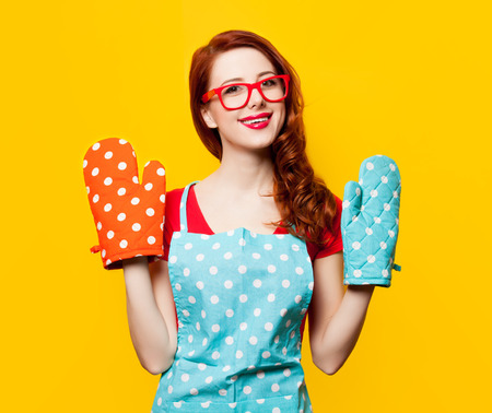 Happy redhead housewife with oven gloves on yellow background Фото со стока