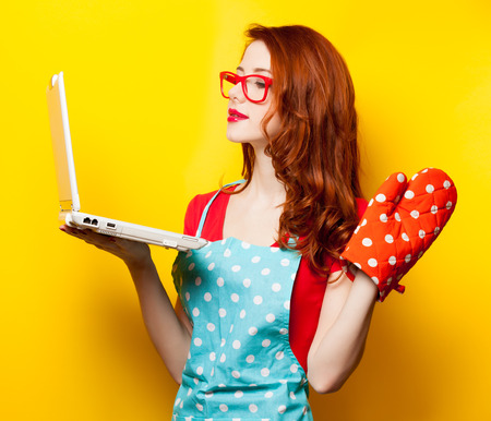 Young housewife with computer and oven gloves on yellow background