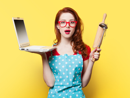 Housewife with computer and plunger on yellow background
