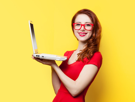 Smiling redhead girl with laptop on yellow background