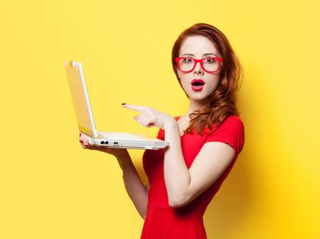 jeune fille: Surpris jeune fille rousse avec un ordinateur portable sur fond jaune Banque d'images