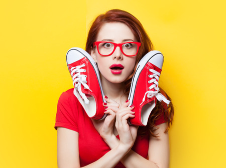 Surprised redhead girl in red dress with gumshoes on yellow background.