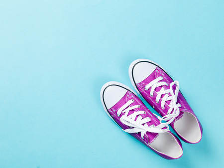 shoelaces: purple gumshoes with white shoelaces on blue background. Stock Photo