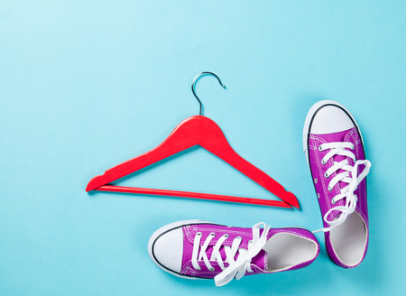 purple gumshoes with white shoelaces and red hanger on blue background. photo