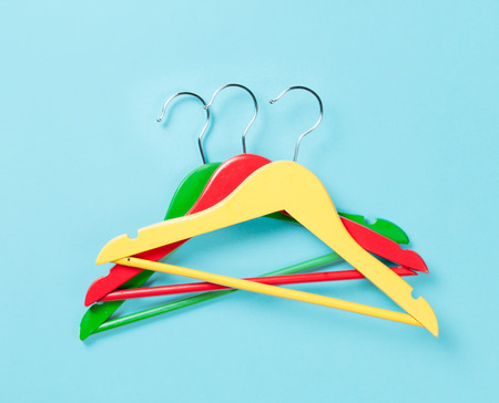 hangers: Three color hangers on a blue background Stock Photo