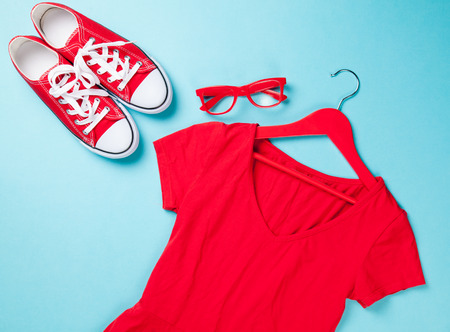 Red gumshoes with white shoelaces and glasses with dress on blue background.