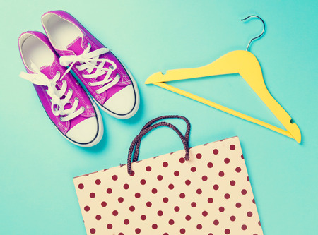 purple: purple gumshoes with white shoelaces and hanger with shopping bag on blue background. Stock Photo